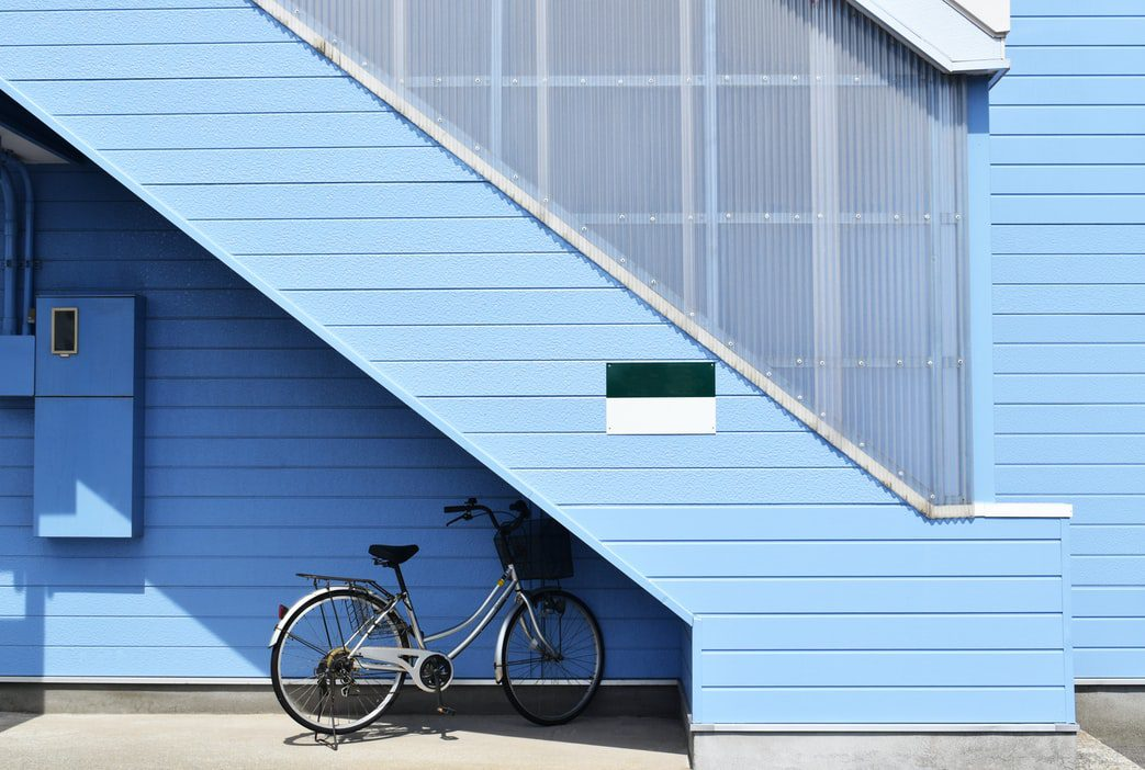 A blue house with a bike leaning on it