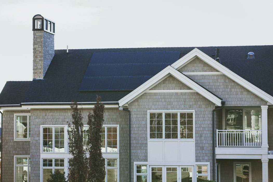 A grey house with solar panels on the roof