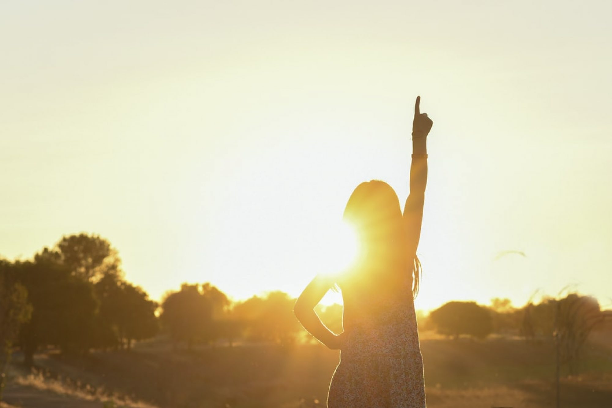 A girl in front of the sun pointing up